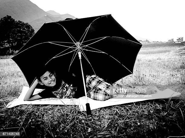 Full Length Portrait Of Smiling Boy With Umbrella Resting On Field