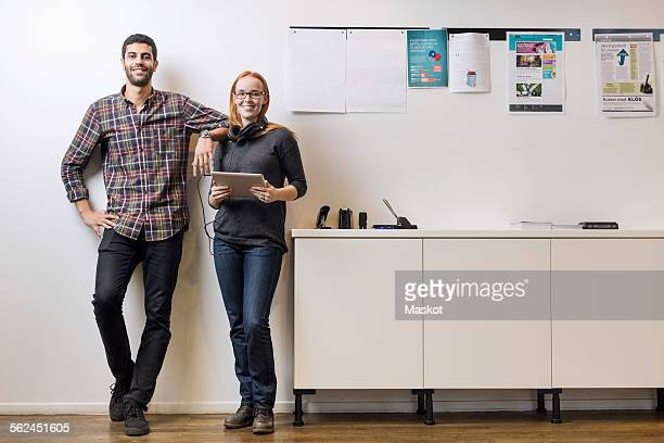 Full length portrait of smiling business colleagues standing by sideboard in creative office