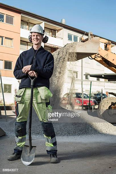 Full length portrait of smiling construction worker with shovel standing at site