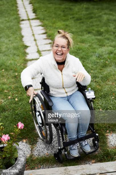 Full length portrait of smiling disabled woman sitting on wheelchair in yard