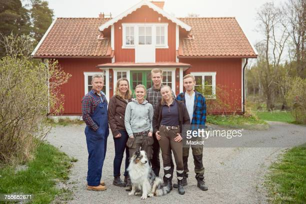 Full length portrait of smiling family standing with Australian Shepherd on footpath