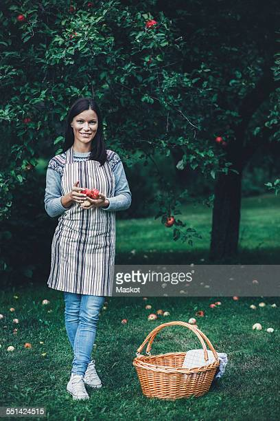 Full length portrait of smiling woman holding fresh apples at orchard