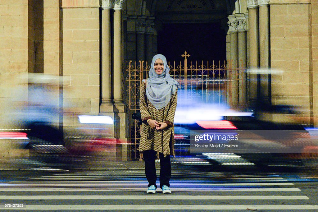 Full Length Portrait Of Smiling Woman In Hijab Standing On City Street With Blur Traffic In Background At Night : Stock Photo