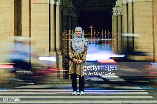 Full Length Portrait Of Smiling Woman In Hijab Standing On City Street With Blur Traffic In Background At Night