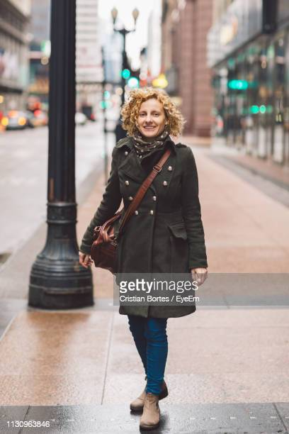 Full Length Portrait Of Smiling Woman Standing On Footpath In City