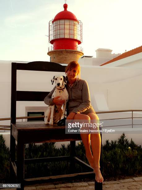 full length portrait of smiling woman with dalmatian sitting on wooden chair against lighthouse during sunset - alleen één mid volwassen vrouw stockfoto's en -beelden