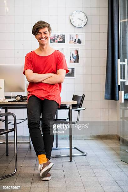 Full length portrait of smiling young businessman with arms crossed in new office