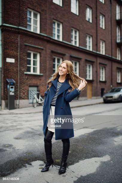 full length portrait of smiling young woman standing with hand in hair on street against building in city - overcoat stock pictures, royalty-free photos & images