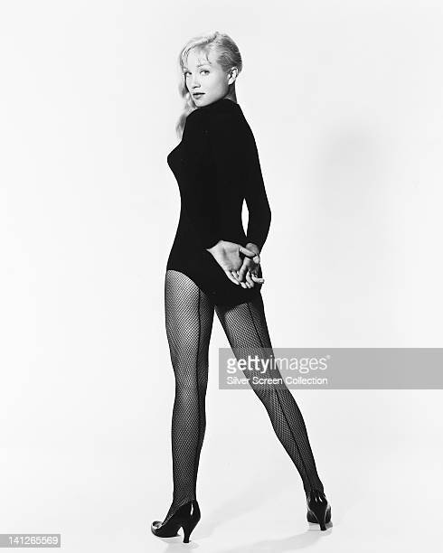 Full length portrait of Susan Oliver US actress wearing a long sleeve leotard and fishnet tights in a studio portrait against a white background...