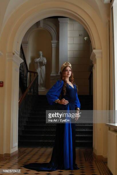 full length portrait of teenage girl wearing royal blue dress standing at palace - royal blue stock pictures, royalty-free photos & images