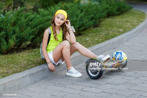 full length portrait of teenage girl with hoverboard sitting at park - hoverboard stockfoto's en -beelden