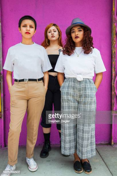 full length portrait of three young latina women - weiblichkeit stock-fotos und bilder
