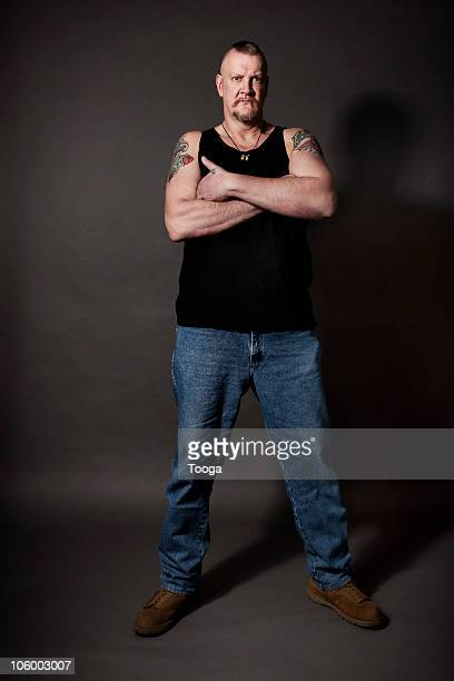 Full length portrait of tough man with tattoos