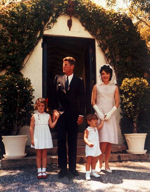 A full length portrait of U.S. president John F Kennedy with first lady Jacqueline Kennedy and their children, Caroline and John Jr, standing outside in front of a door at his father Jospeh P Kennedy's estate, Palm Beach, Florida, Easter Sunday, April 14,