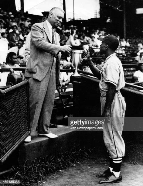 A full length portrait of US representative Arthur Wergs Mitchell presenting a cup to captain Sylvester Hall of the Police Boy's Club baseball team...