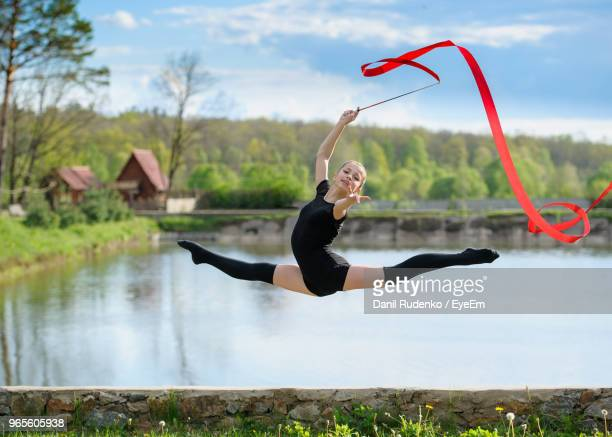 full length portrait of woman gymnast jumping in air while holding ribbon against lake - rhythmic gymnastics stock pictures, royalty-free photos & images