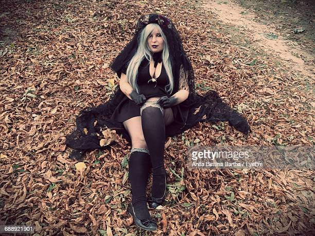 Full Length Portrait Of Woman In Gothic Style Clothing Sitting On Field In Park During Winter