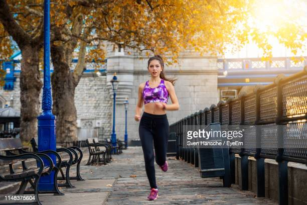 full length portrait of woman running on footpath - running stock pictures, royalty-free photos & images