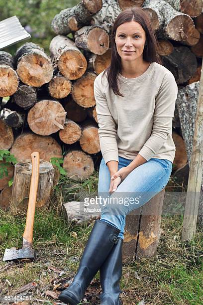 Full length portrait of woman sitting on tree stump against stacked firewood at yard