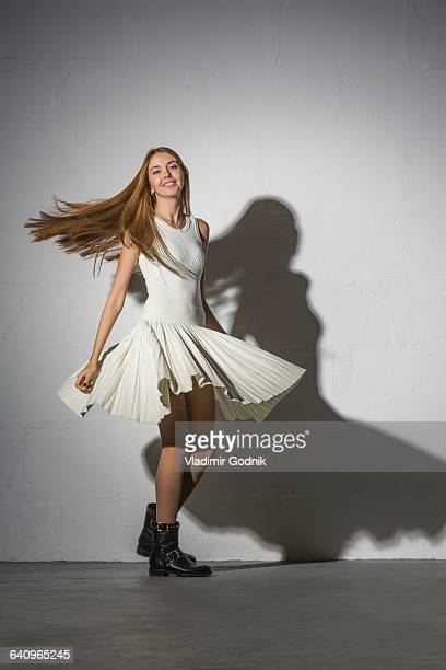 Full length portrait of woman spinning against white background
