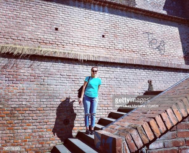 Full Length Portrait Of Woman Standing On Steps Against Building During Sunny Day