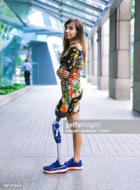 Full Length Portrait Of Woman With Prosthesis Leg Standing On Footpath
