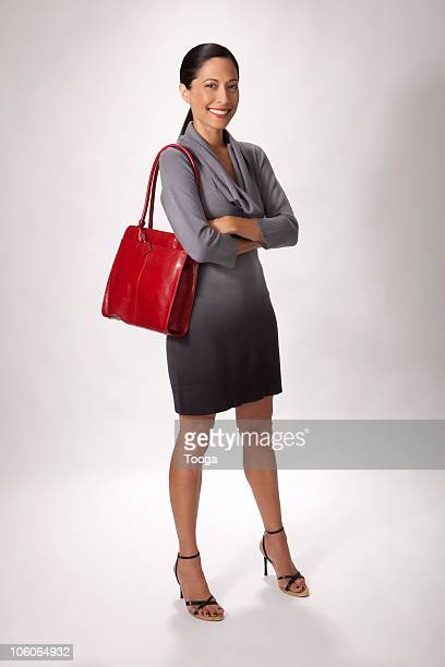 full length portrait of woman with red purse - ショルダーバッグ ストックフォトと画像