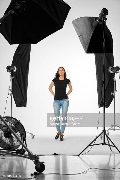 full length portrait of woman with umbrella lights standing against white backdrop in studio - fotosession stock-fotos und bilder