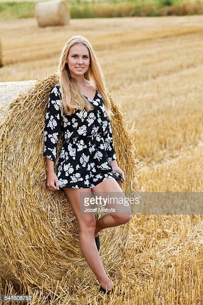 full length portrait of young blonde woman on field - miniklänning bildbanksfoton och bilder