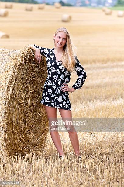 Full length portrait of young blonde woman on field
