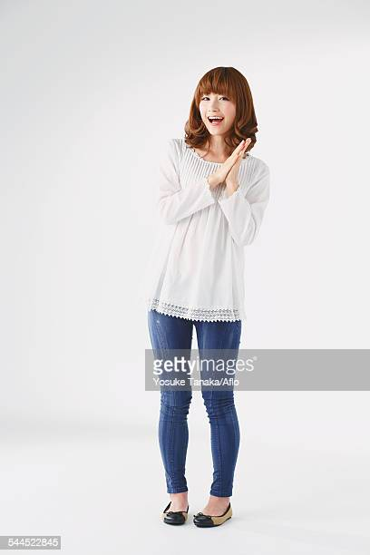 full length portrait of young japanese woman against white background - 手をたたく ストックフォトと画像