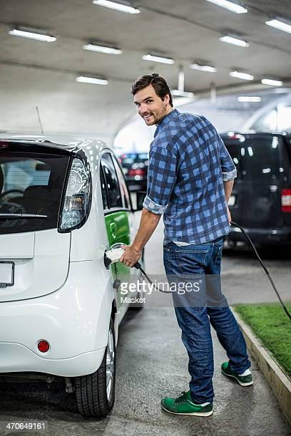 full length portrait of young man charging electric car at gas station - elektroauto stock-fotos und bilder