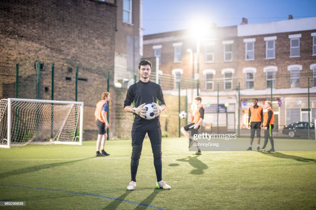 Full length portrait of young man holding football on pitch with players in background : Stock Photo