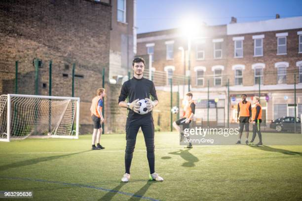 full length portrait of young man holding football on pitch with players in background - amateur stock pictures, royalty-free photos & images