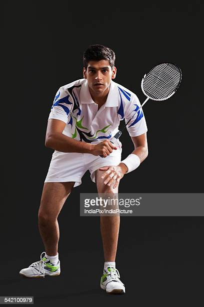Full length portrait of young man playing badminton over black background