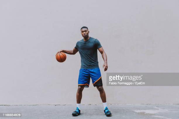 full length portrait of young man playing basketball against wall - dribbling stock pictures, royalty-free photos & images