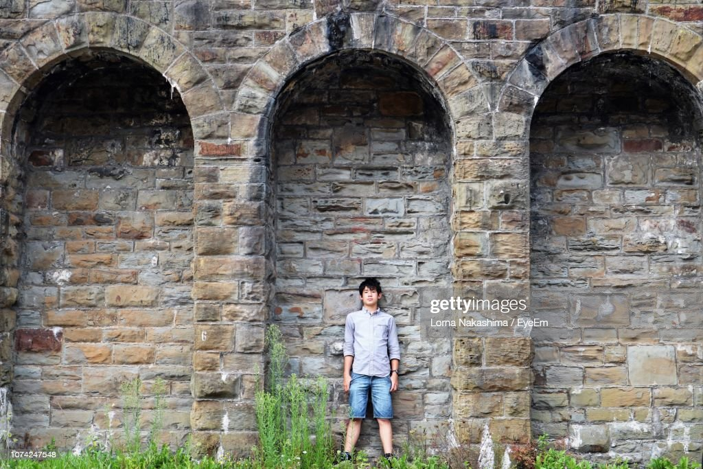 Full Length Portrait Of Young Man Standing Against Brick Wall : Stock Photo