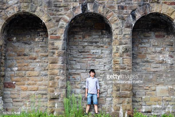 Full Length Portrait Of Young Man Standing Against Brick Wall