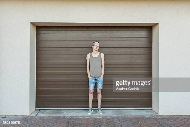 Full length portrait of young man standing against garage door