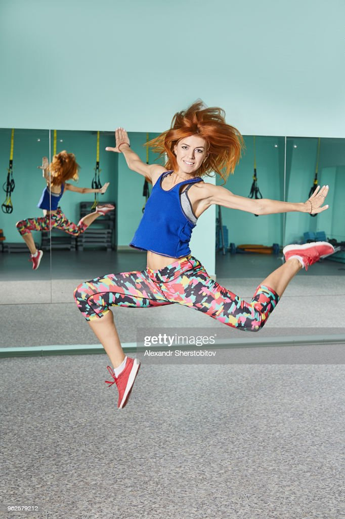 Full length portrait of young woman jumping in mid-air at health club : Stock Photo