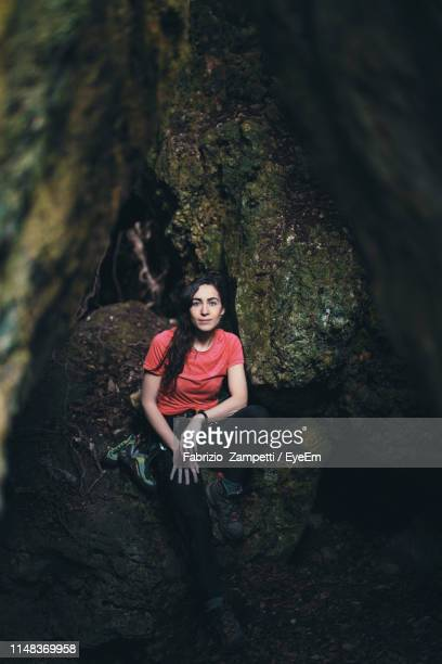 full length portrait of young woman leaning on rock in forest - fabrizio zampetti foto e immagini stock