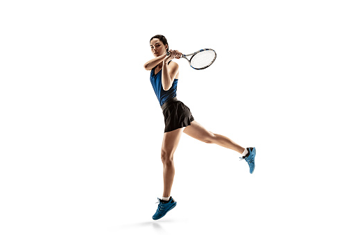 Full length portrait of young woman playing tennis isolated on white background 1095942544