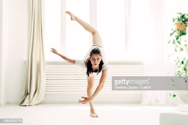 full length portrait of young woman practicing yoga in warrior position at home - standing on one leg stock pictures, royalty-free photos & images