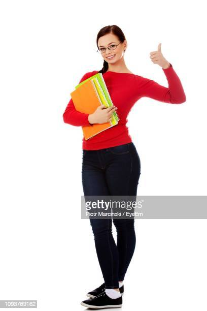 full length portrait of young woman showing thumb up while holding books against white background - long sleeved stock pictures, royalty-free photos & images
