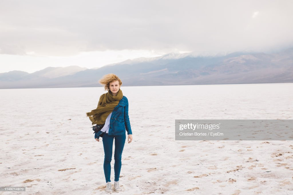 Full Length Portrait Of Young Woman Standing In Desert Against Sky : Stock Photo