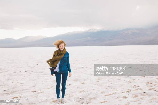 full length portrait of young woman standing in desert against sky - bortes stock photos and pictures