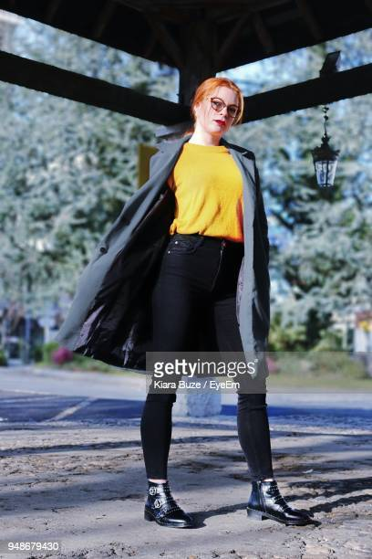 full length portrait of young woman standing in gazebo - coat ストックフォトと画像