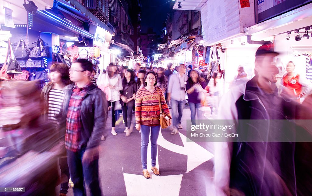 Full Length Portrait Of Young Woman Standing On City Street Amidst Crowd : Stock Photo