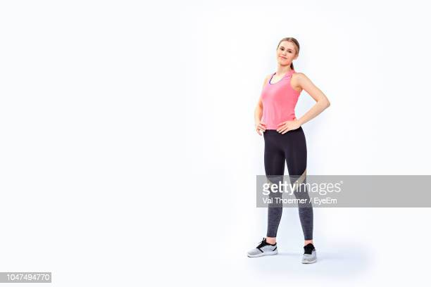 full length portrait of young woman standing on white background - stehen stock-fotos und bilder