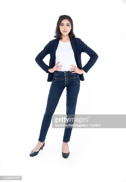 full length portrait of young woman standing on white background - hand on hip stock pictures, royalty-free photos & images